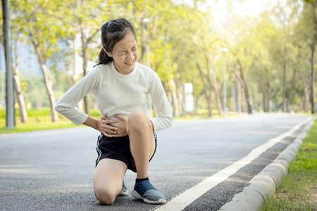 Fille d'enfant asiatique malade tenant ses mains sur le ventre ayant l'estomac douloureux dans l'attaque d'appendicite du côté droit, une adolescente souffre de maux d'estomac ressentant une douleur aiguë, des symptômes d'appendicite au parc
