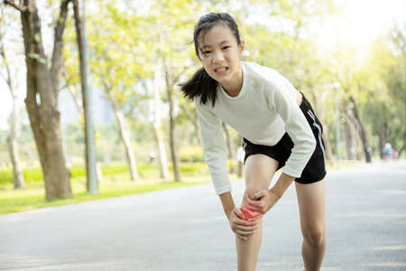 Unhappy asian child girl injured her leg pain or calf muscle while playing in sunny day, female teenage holding hands on the legs,feel pain in the knee from exercise in summer,physical injury concept