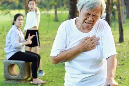 Asian elderly people having heartbeats fast,difficulty breathing,symptoms of heart problem while walking exercise in outdoor park,senior woman with chest pain suffer from heart attack,health care Standard-Bild - 134653519