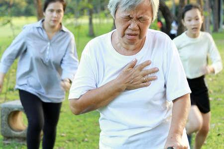 Asiatische ältere Frau, die Schwierigkeiten beim Atmen hat, leidet an Herzinfarkt, Herzproblemen beim Gehen im Park, Tochter und Enkelin laufen, um zu helfen, ältere Mutter, die Brustschmerzen hat