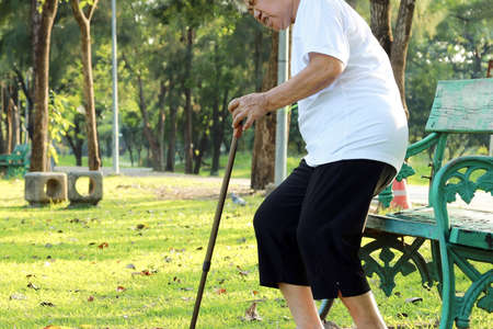 Unhappy asian senior woman suffering from hemorrhoids,elderly person is afraid of the pain in her buttocks from hemorrhoids, carefully sitting on bench in the park,feel bottom in pain,health problem