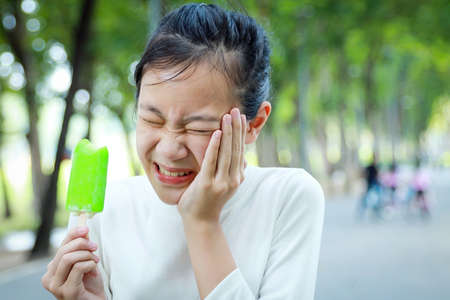 Asian child girl holding her hand on her aching tooth have hypersensitive teeth eating ice-cream,feel painful,female teenage have sensitive teeth problem with ice-lolly,tooth decay,dental care concept Фото со стока - 134654834