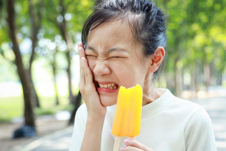 Asian child girl having hypersensitive teeth eating ice-pop,feel painful,female teenage have sensitive teeth with ice-lolly,sad woman suffer toothache and tooth decay,dental care,health care concept Фото со стока - 134654844