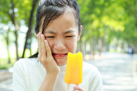 Asian child girl have hypersensitive teeth eating ice-cream,feel painful ,female teenage have sensitive teeth problem with ice-lolly,woman suffering toothache and tooth decay,dental care concept