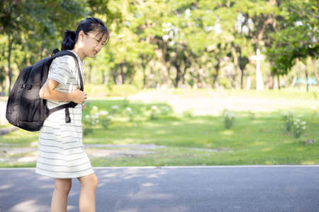 Asian child girl carrying heavy school bag or backpack,teenage feeling unhappy and pain on back, full of books on her back, going to school for the first time, tired student back to school learning Standard-Bild - 134654862