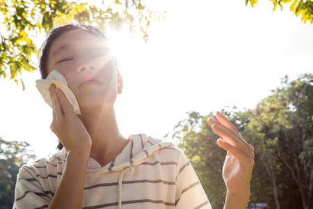 Asian child girl wiping sweat on her face with tissue paper suffer from sunburn very hot in summer weather problem feel faint, tired female teenage with heat stroke,high temperature on sunny day Standard-Bild - 134654870