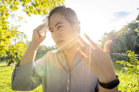 Asian woman wiping sweat on face with tissue paper suffer from sunburn very hot in summer weather problem feel faint, tired female people with heat stroke,high temperature on sunny day,global warming Standard-Bild - 134654986