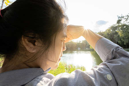 Asian woman have conjunctivitis,cataract,young female covering face by hand of bright sun in outdoor on sunny day,feel dizzy,risk of eye damage from ultraviole(UV rays),photophobia,eye health concept Zdjęcie Seryjne