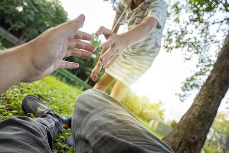 Enfant asiatique aidant l'homme à se lever de l'herbe après être tombé à cause d'un accident, jouant avec elle au parc, sa fille tirant la main et encourageant son père Banque d'images