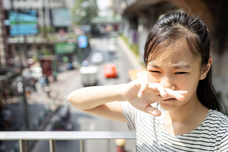 Asian child girl catches her nose because toxic fumes from car,bad smell,air pollution,dust allergies or sinus infection,female teenage rubbing nose suffer from allergic in city,life of urban people