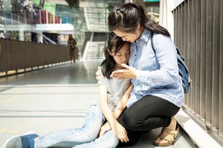 Asian mother help her daughter support while her teen daughter fainted unconscious while walking outside,tired child girl with heat stroke on a sunny day suffer from sunburn very hot in summer outdoor
