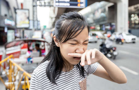Asian child girl catches her nose because toxic fumes from car,bad smell,air pollution,dust allergies or sinus infection,female teenage rubbing nose suffer from allergic in city,life of urban people Standard-Bild - 134654990