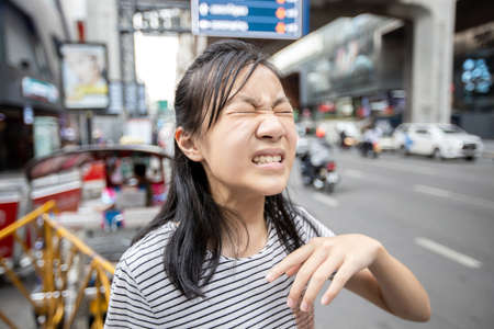 Asian child girl with a burning sensation,eye irritation from car smoke in the city,feel eyes pain,dust,ocular allergy with closed eyes effect of air pollution,teenage on street in toxic environments Zdjęcie Seryjne