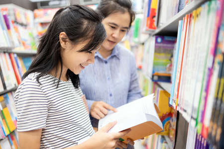 Asian child girl selecting book from a bookshelf with their mother reading books together while visiting book shop,teenage student feel enjoy study in bookstore,happy school girl relax by reading book
