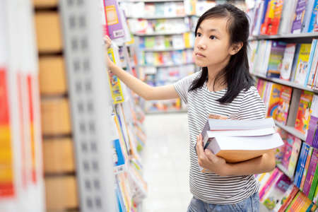 Asian child girl selecting book from a bookshelf,female student shopping or chooses a book in bookstore,searching books,teenage relax by reading books,concept of learn,read,study and education Stockfoto