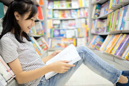 Smiling asian child girl sitting reading a book on the floor,teenage student searching in formation in textbook for coursework feel enjoying study in library,happy woman relaxing,education concept