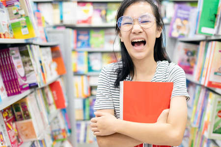 Smiling asian child girl wearing glasses holding a book on her arms,female student standing feel enjoy in book store,happy woman is laughing, relax by reading books,concept of development,education