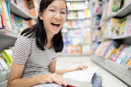 Smiling asian child girl wearing glasses sitting reading a book on the floor,teenage student feel enjoying study in library,happy school girl relax by reading books, learn, read and education concept Zdjęcie Seryjne