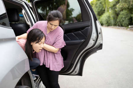 Aziatisch kindmeisje dat op het punt staat over te geven van wagenziekte of indigestie, vrouwelijke tiener die overgeeft in een auto lijdt aan bewegingsziekte, dochter duizelig van wagenziekte, moeder helpt, voor haar zorgt, gezondheidszorg
