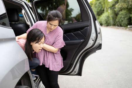 Bambina asiatica che sta per vomitare dal mal d'auto o dall'indigestione, adolescente femminile che vomita in un'auto soffre di cinetosi, figlia che ha le vertigini per il mal d'auto, madre che aiuta, cura di lei, assistenza sanitaria