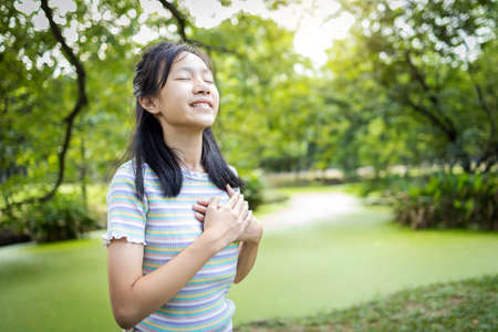 Happy smiling asian child girl standing in green nature,holding hands on heart,female teenage touching her chest,enjoy breathing fresh air with closed eyes,relaxing in park,healthy lifestyle concept Standard-Bild - 134655005