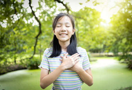 Happy smiling asian child girl standing in green nature,hold hands on heart,feel peace of mind,female teenage closed eyes,enjoy breathing fresh air dreaming,relax in park,healthy mental health concept Standard-Bild - 134655006
