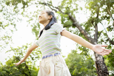 Happy smiling asian child girl standing with arms outstretched in green nature,female teenage enjoy breathing fresh air with raised arms up and closed eyes having fun,relax in park,healthy lifestyle Zdjęcie Seryjne