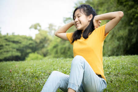Happy asian child girl resting feel comfortable at park,female teenager with hands behind her head and closed eyes,healthy woman enjoy breathing fresh air,relaxing in green nature after studying Standard-Bild - 134655013