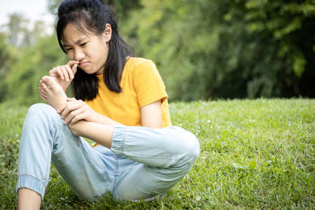 Unhappy asian female teen is sniffing her feet smell,hold her foot in her hand,stink legs,unpleasant smell,child girl with bad smell,accumulated dirt,emotion facial expression,foot skin care problem Standard-Bild - 134655015
