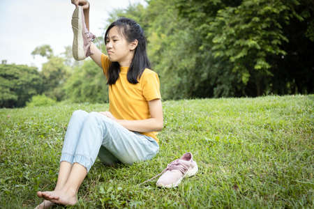 Unhappy asian female teenage is sniffing her sneakers,hold stinky shoe in hand,unpleasant smell,hot weather or after exercise,child girl with disgust,bad smell,health care,Pitted Keratolysis concept Standard-Bild - 134655023