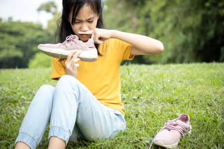 Asiatische Teenagerin schnüffelt an ihren Turnschuhen, hält stinkenden Schuh in der Hand, unangenehmer Geruch, heißes Wetter oder nach dem Training, Kindermädchen kneift die Nase mit Ekel im Gesicht, sehr übler Geruch, etwas stinkt Standard-Bild