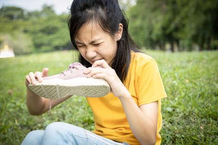 Asiatische Teenagerin schnüffelt an ihren Turnschuhen, hält stinkenden Schuh mit Ekel im Gesicht in der Hand, unangenehmer Geruch wegen heißem Wetter oder nach dem Training, Mädchen mit schlechtem Geruch, angesammelter Schmutz