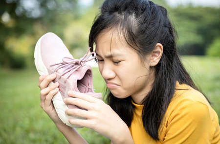 Unhappy asian female teenage is sniffing her sneakers,hold stinky shoe in her hand with disgust,unpleasant smell because of hot weather or after exercise,sad child girl with bad smell,accumulated dirt