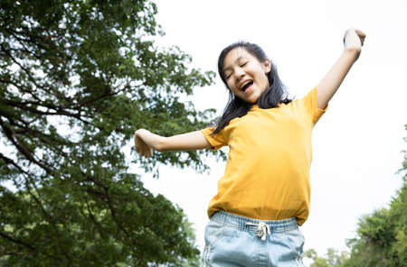 Happiness asian woman standing feel comfortable at park,smiling female teenage with stretching her arms,enjoy breathing fresh air,freedom and relaxing in green nature after school,lifestyle concept Standard-Bild - 134656878