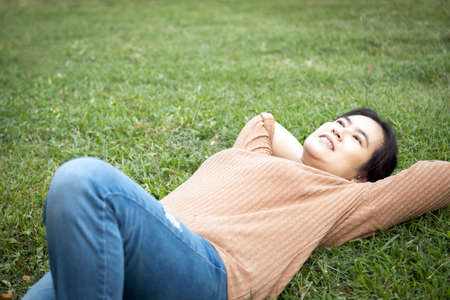 Happy asian woman resting feel comfortable while lying on the grass at park,female people with hands behind her head,enjoy breathing fresh air,relaxing in green nature after housework on weekend