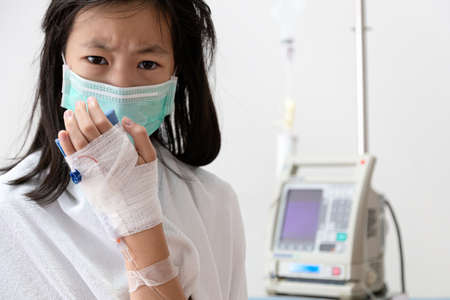 Sick asian child girl wearing medical mask has a cough,cold and high fever,treatment from saline medicine with infusion pump,female patient with medical equipment in room of hospital ward suffering from influenza,health care,medical concept Standard-Bild - 134656883