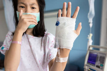 Sick asian child girl wearing medical mask has a cough,cold and high fever,treatment from saline medicine with saline solution controller,woman patient with medical equipment suffer from influenza,health care,medical concept