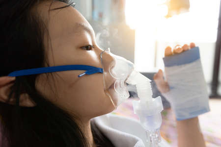 Closeup of sick asian child girl wearing oxygen mask has problems with the respiratory disease,treatment from oxygen therapy,female patient put inhalation suffer from asthma,influenza virus in hospital bed,health care,medical concept Zdjęcie Seryjne
