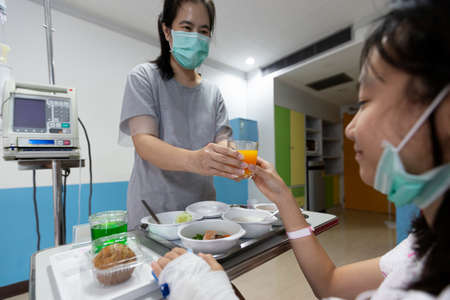 Asian child girl is on drip receiving a saline solution,female patient eating food in room of hospital ward,smiling mother giving orange juice to sick daughter suffer from influenza,health care, support concept Zdjęcie Seryjne