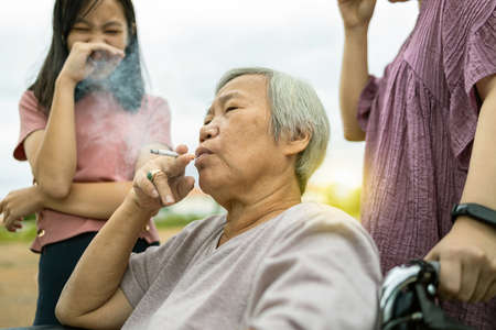 Asian senior woman holding a cigarette smoking,smokers elderly smoking near people in family,daughter, granddaughter closing nose,pollution from cigarettes smoke,dangerous to health,addiction,life