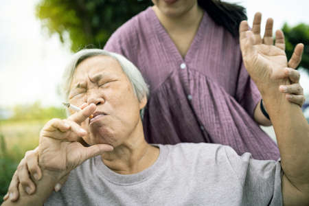 Asian senior mother holding a cigarette smoking,female old in wheelchair smoking near daughter,woman request elderly people to stop smoking,bad smell,pollution from cigarettes smoke,health care,life Stock fotó