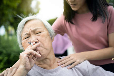 Asian senior grandmother hold a cigarette smoking,old people or smoker smoking near granddaughter,child girl request elderly woman to stop smoking, bad smell,smelling pollution, health care,lifestyle