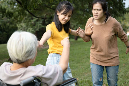 Asian teen granddaughter dissuade her family from a big fight,angry senior mother ,aggressive daughter arguing violently,abusing,quarreling at park while traveling together,ungrateful,family problems Stock fotó