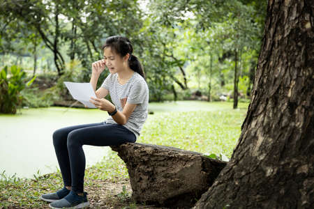 Sad asian child girl sit alone and crying,reading letter,bad news,female teenage student received school notice letter to her about her academic performance slump,disappointed with her education Stockfoto
