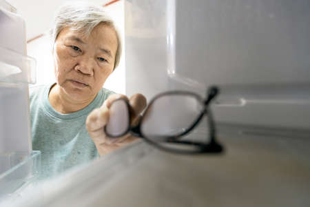 Asian senior woman with memory impairment symptoms,forget her glasses in the refrigerator or storing glasses in the fridge,female elderly having dementia, cognitive impairment, alzheimers, amnesia