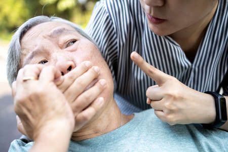 Angry asian woman covering senior mouth and showing silence gesture, keep a secret be quiet,social violence,aggression, scared elderly people with female caregiver,bad relationship,physical abuse Stock Photo