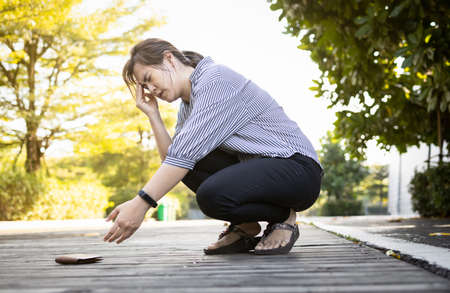Exhausted asian woman suffer from headache,migraine,tired female people having vertigo,feel dizzy,fatigue,fainted while stooping down,reached towards her wallet that had fallen on floor,health care