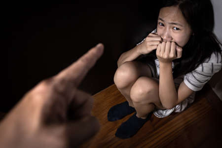 Sad asian child girl sit on floor,feel fear,pain,cry, stop physical abuse and domestic violence, angry man or father scolds frightened daughter,campaign against violence and aggression concept