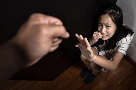 Asiatisches Kindermädchen, das auf dem Boden sitzt und Handzeichen zeigt, um aufzuhören, körperlichen Missbrauch und häusliche Gewalt zu stoppen, wütender Mann oder Vater erhob die Straffaust, Tochter ist unterdrückt, Mobbing fühlt sich ängstlich an, weint Standard-Bild