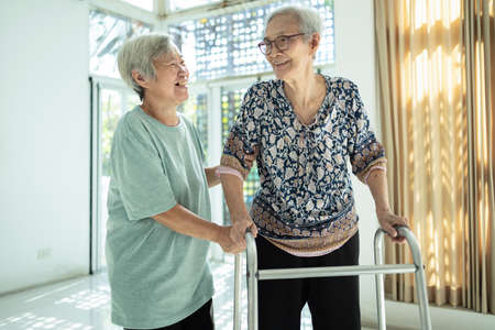 Asian female senior with walker and elderly woman nostalgic and visit her childhood friend at home,happy two old people having fun talk,enjoy,laughing together,real friend,close friend,care,support